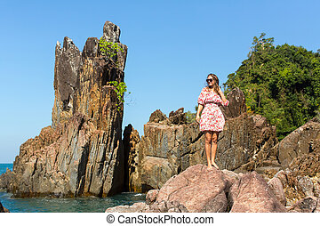Woman standing among the rocks.