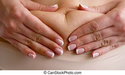 Woman standing and grabbing her tummy with her hands