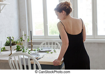 Woman standing and leaning on table