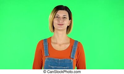 Woman standing and looks at the camera. Green screen