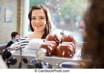 Woman Standing At Counter In Coffeeshop