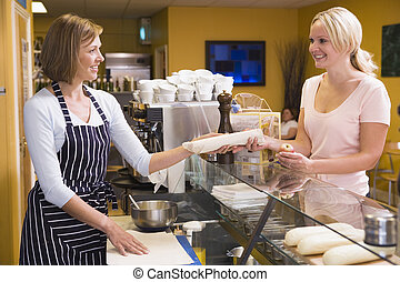 Woman standing at counter in restaurant serving customer and smi