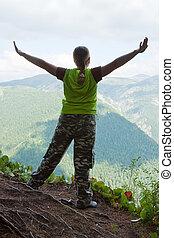 woman standing at mountain peak
