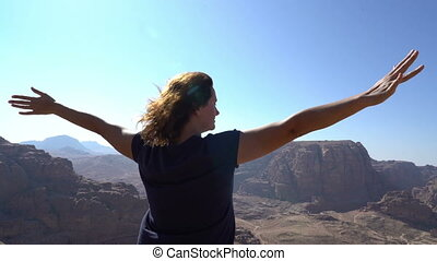 woman standing at point view in the middle of mountains ...
