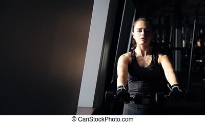 Woman standing at the window smiling and engaged with dumbbells
