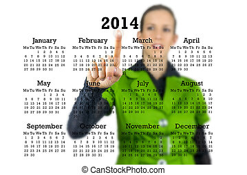 Woman standing behind a 2014 calendar