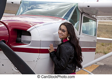 Woman standing by airplane cowling