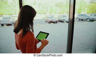 Woman standing by the window and work on tablet . green screen
