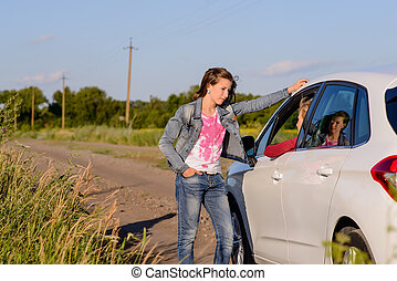 Woman standing chatting to her friend in a car at the side ...