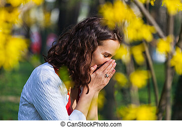 Woman standing close to flowers is sneezing