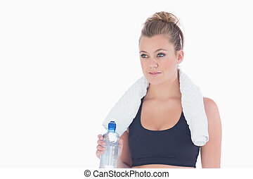 Woman standing holding a bottle of water and a towel