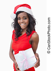 Woman standing holding a gift while smiling