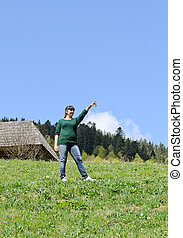 Woman standing in a green field pointing
