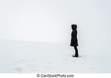 Woman standing in a snowy field