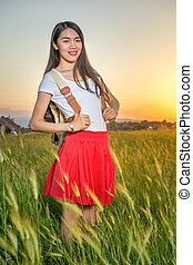 Woman standing in a wheat field at sunset