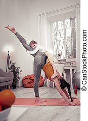 Woman standing in balancing yoga pose with her child