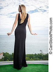 Woman standing in black fashion dress