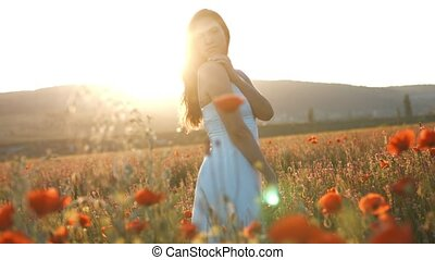 Woman standing in blossom poppies field