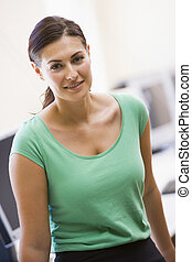 Woman standing in computer room smiling