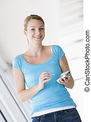 Woman standing in corridor using personal digital assistant smil