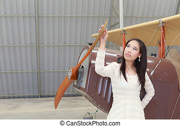 Woman standing in front of a classic light aircraft