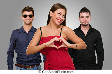 Woman Standing In Front Of Men Making A Heart Shape Sign On...