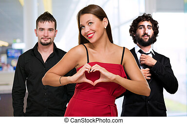 Woman Standing In Front Of Men Making A Heart Shape Sign,...