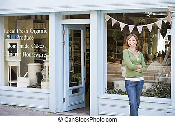 Woman standing in front of organic food store smiling