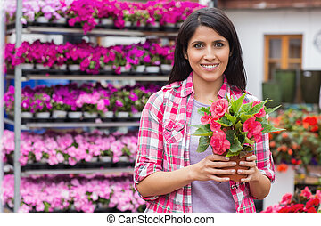 Woman standing in front of shelves and holding a flower