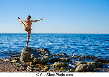 Woman standing in Hand to Toe pose near sea