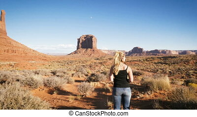 woman standing in Monument Valley with red rocks overview.