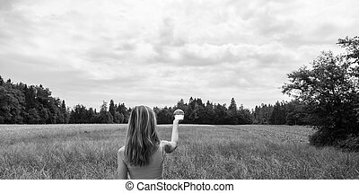 Woman standing in nature holding crystal ball