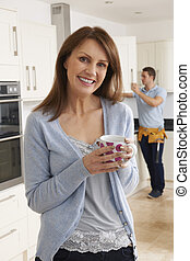 Woman Standing In New Fitted Kitchen With Workman