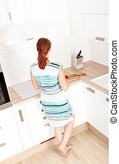 Woman standing in new kitchen.