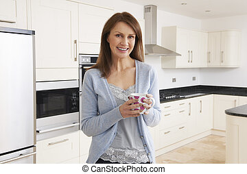 Woman Standing In New Luxury Fitted Kitchen