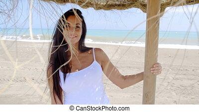 Woman Standing in Shade of Sun Umbrella on Beach