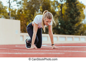 Woman standing in start position for run