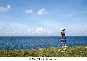Woman standing in summer by seaside wathing the horizon