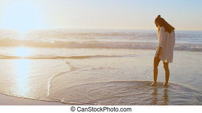 Woman standing in the beach at dusk 4k - Rear view of woman...