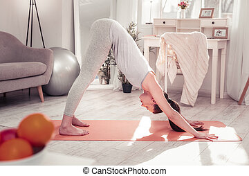 Woman standing in the downward-facing dog pose while practising yoga