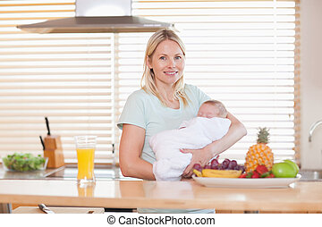 Woman standing in the kitchen while holding her baby