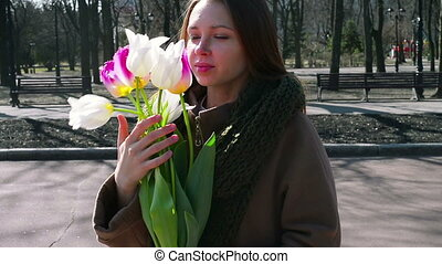Woman standing in the park and holding bouquet of white
