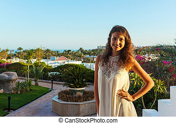 woman standing in the park. Beautiful young woman smiling on a background of palm trees and sea
