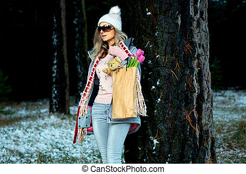 Woman standing in the snow under big old growth pine trees