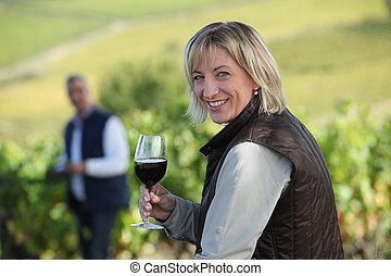 Woman standing in vine rows with glass of wine