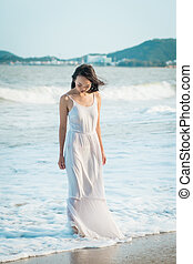 Woman standing in wave on beach in summer. Happy multiracial Asian girl going to sea.