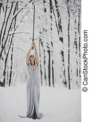 Woman standing in winter forest with sword over her head