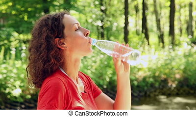 woman standing in woods and drinking water
