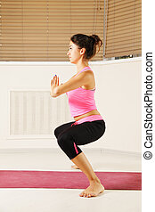 Woman standing in yoga pose sideview