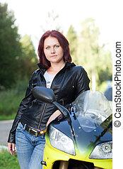 woman standing near bike - beautiful young woman standing at...